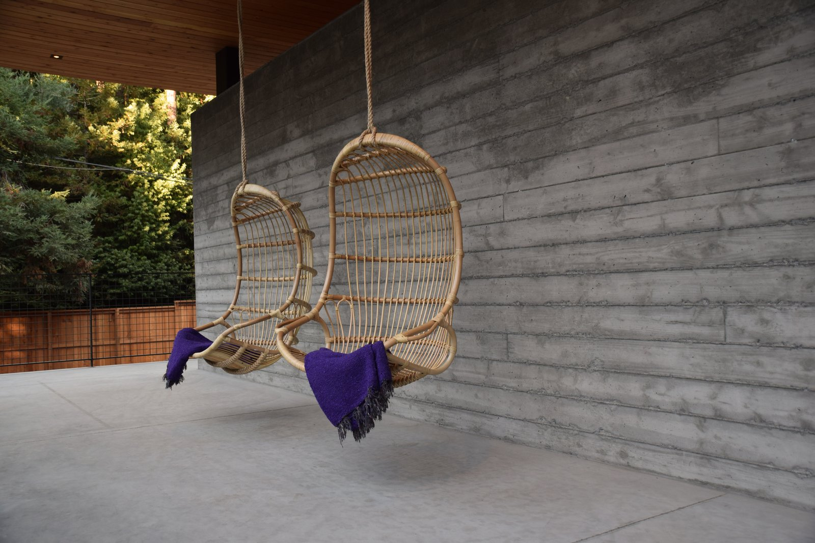 Hanging rattan chairs invite guests to curl up with a cup of tea and enjoy views of the meadow.