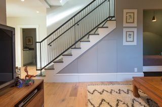 When connecting the basement level to the rest of the home, Wendi Sue chose a contemporary railing that would still cohere with the more traditional vernacular throughout. The custom steel stairwell features a matte black powder finish and pickets of tensioned military parachute cord.