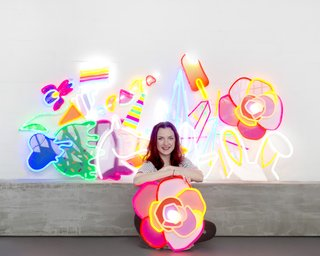 Natalie Jarvis poses with her creations. When she initially conceived of Electric Confetti, she had considered using traditional neon, but its fragility and the presence of mercury drove her to research other alternatives—leading to her discovery of LED neon flex.