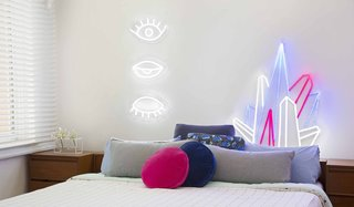 Eye! Eye! Eye! ($449) and Crystal Prism ($449) decorate a bedroom. Electric Confetti's designs come with a remote control that allows you to dim the neon to less than 5% brightness, ideal for a nightlight, or set it to an adjustable flashing speed.