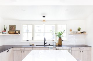 """A white undermount sink and a matte black faucet are functional, refined elements. """"The one thing I did love about the previous kitchen was the large window over the sink, and that's the only design element we chose to keep,"""" says Lewis."""