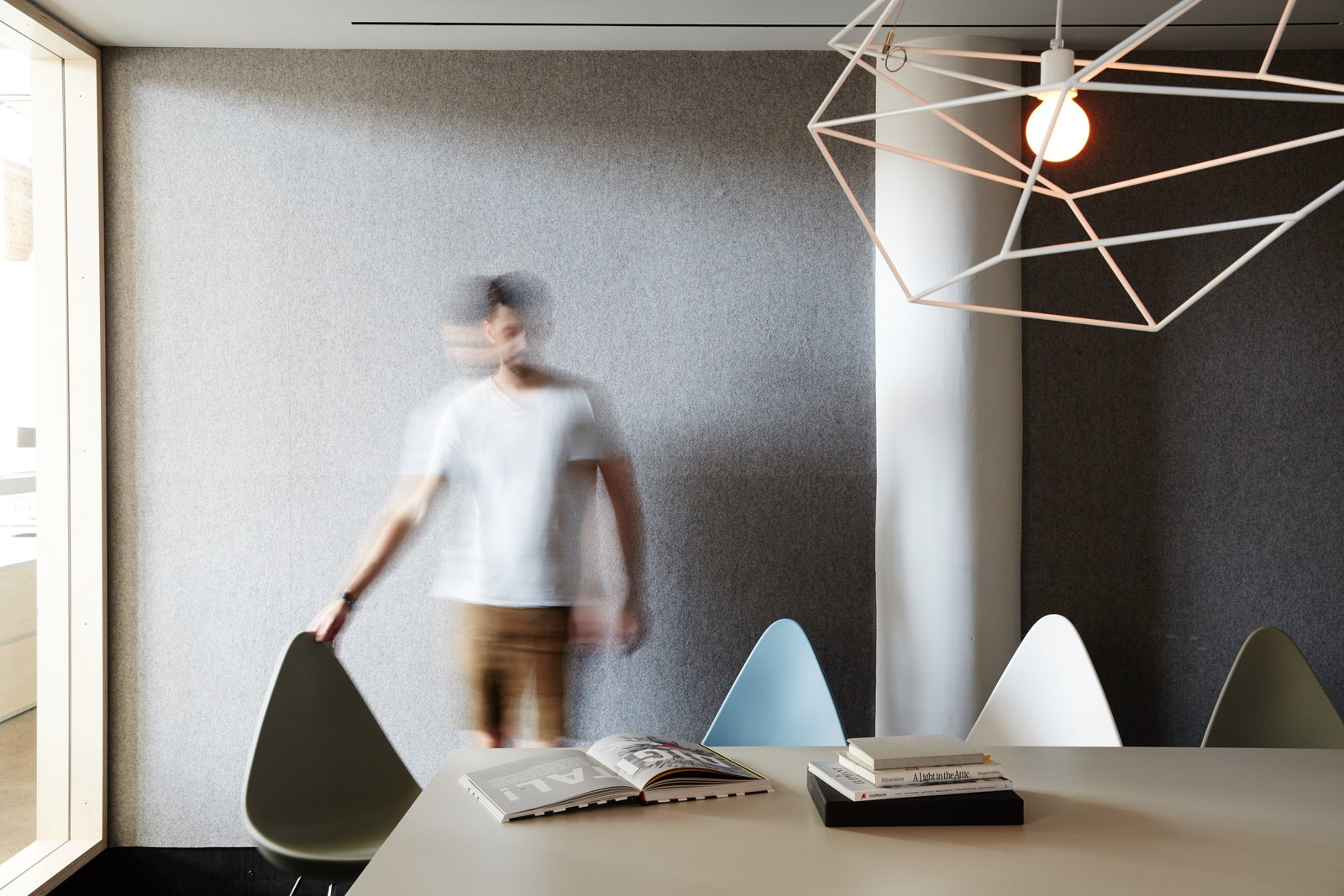 A large meeting room, equipped with Drop Chairs by Fritz Hansen and a sculptural Spica Light by Iacoli & McAllister, seats 14.  Photo 4 of 12 in Space to Work, Room to Play