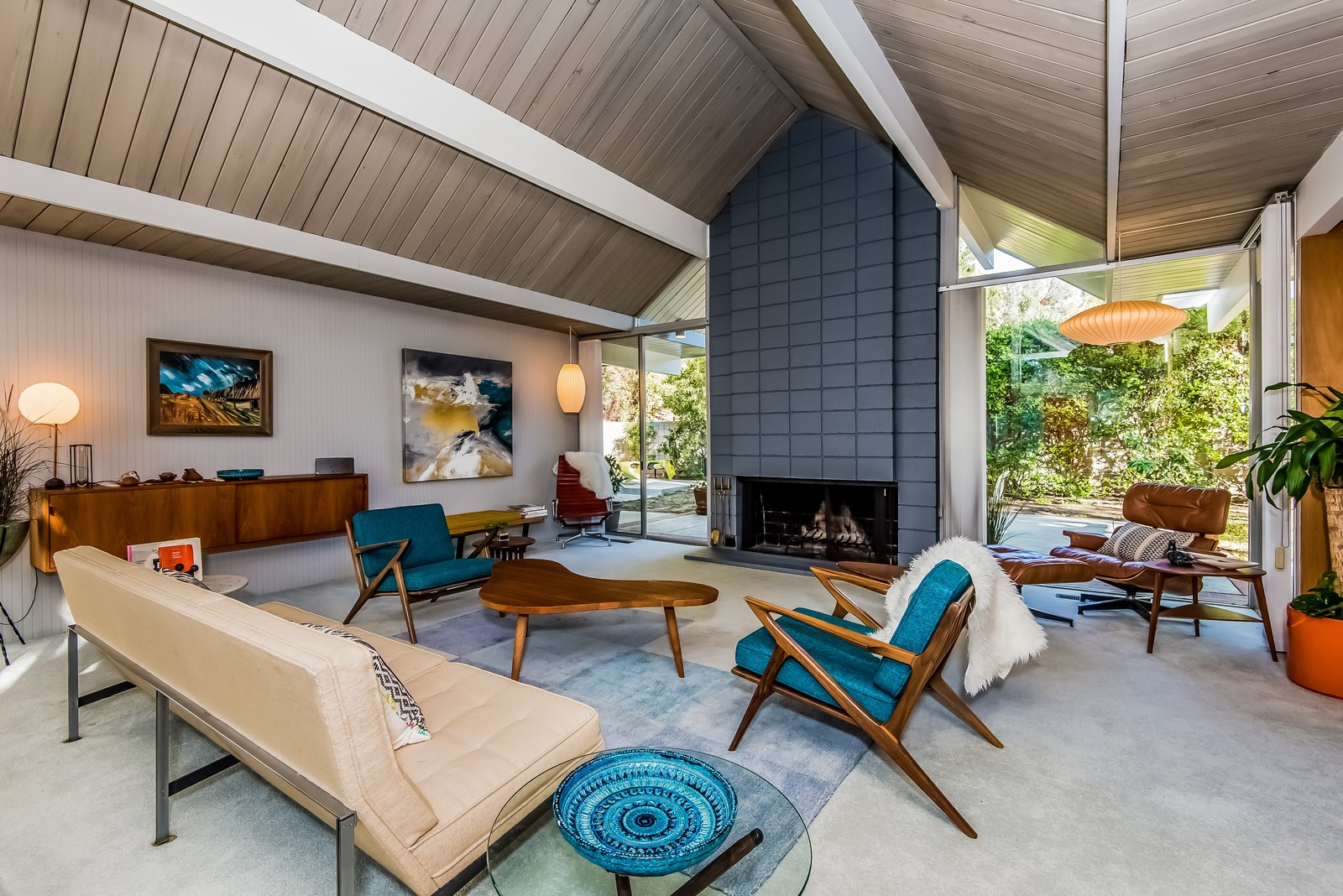 The George Nelson Cigar and Saucer Pendant Lamps are original, and also available for purchase. A cinderblock fireplace provides an inviting focal point.  Photo 5 of 13 in With Only One Previous Set of Owners, a Pristine Eichler Home Asks $799K