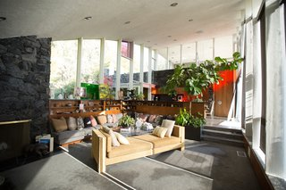 """Tackling Big Design Questions in an Iconic Home - Photo 2 of 9 - A realtor nicknamed the residence """"The Rainbow House"""" for the colored glass that punctuates its arched walls. In the living room, where the panel was held, daylight casts a red streak into the kitchen and dinette area."""