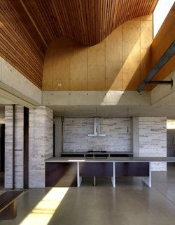 The light scoop illuminates a ceiling of sinuous plywood slats.