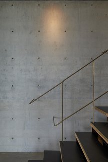 The slim brass rods of the stair railing in this countryside house in Australia create a shimmering silhouette against the matte texture of the concrete wall. The rods die gracefully into the wall of the concrete, and the notes of brass are picked up by the concrete plugs inserted into the panels.