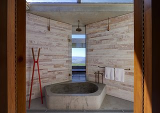 A centrally placed bathroom features an oversized concrete tub and bespoke brass and copper fixtures. A slim pane of glass allows you to take in views beyond the open terrace and firepit, while the glass ceiling exposes the room to the changing sky.