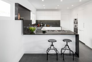 "In a kitchen that Brunn built using Bosch appliances, an understated black-and-white palette is paired with a minimal design. The project was named Wrap It Up as an allusion to the way the Caesarstone runs up the wall to create a shelf. ""Anytime we do a project,"" says Brunn, ""we have to do something different and push the boundaries."" The shelf also hides a secret compartment where the homeowner can slide in a cutting board for easy, accessible, and hygienic storage."