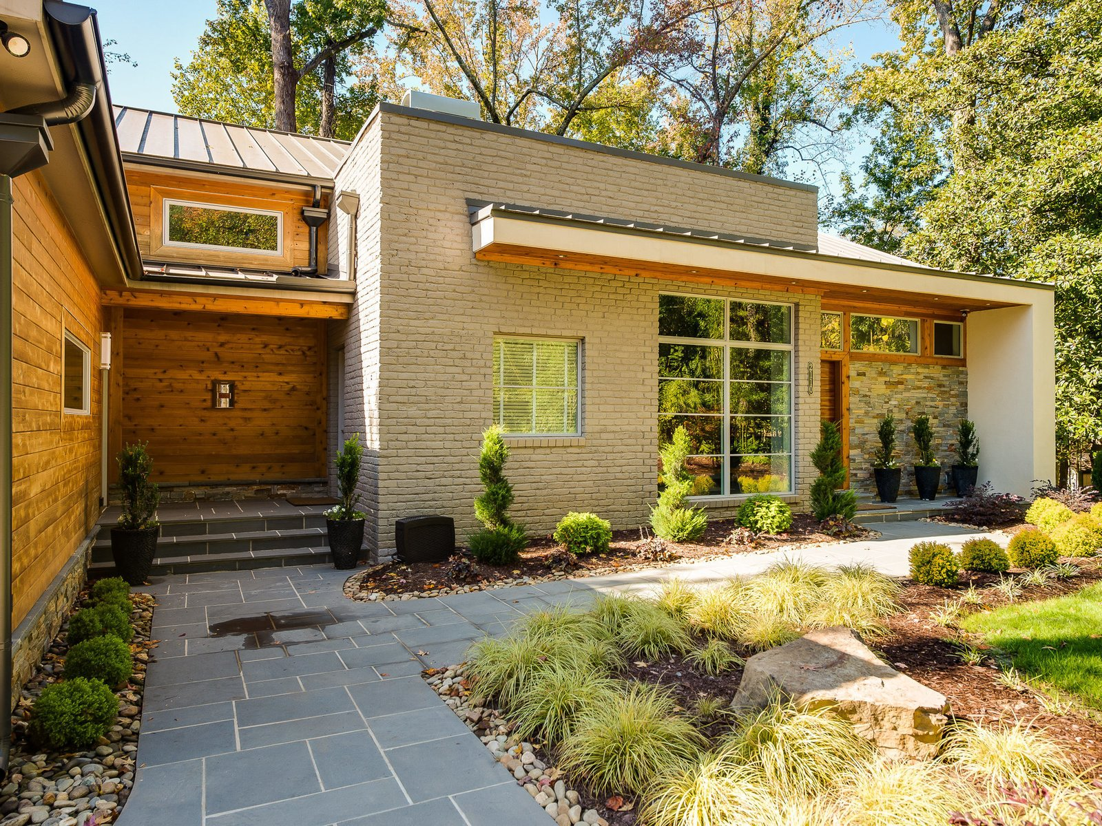 The landscaping features encore azaleas, arborvitae, and Japanese cypress. An oak forest in the backyard provides a sense of privacy and seclusion.  Photo 4 of 11 in Move Into This Midcentury Modern Revival in North Carolina For $1.2M