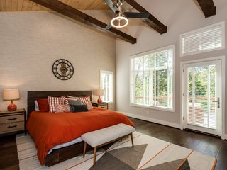 Three exposed beams run across the vaulted cedar ceiling in the master bedroom, which has private access to the back deck. The generous closet features custom built-in wood shelving  and a packing island with a granite top.