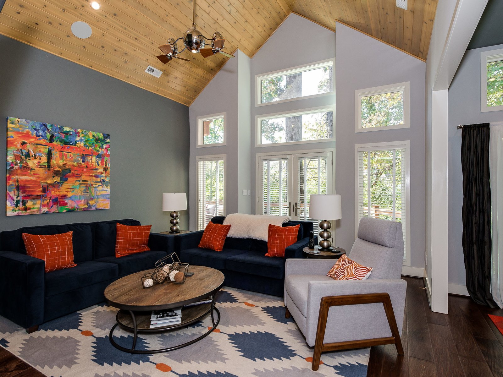 On the other side of the fireplace is the great room, where a vaulted cedar ceiling, measuring 18 feet at its height, adds to the feeling of spaciousness. The French doors lead to the balcony.  Photo 8 of 11 in Move Into This Midcentury Modern Revival in North Carolina For $1.2M