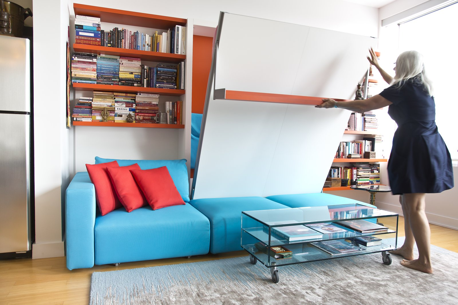 Annette demonstrates the ease of lowering the Swing, a queen-size wall bed with nine-foot sofa and sliding chaise. Here, it integrates with a shelving system, which continues the apartment's quirky motif of orange and blue.  Photo 4 of 6 in Two Film Industry Veterans Flip the Script With a Suburb-to-City Move