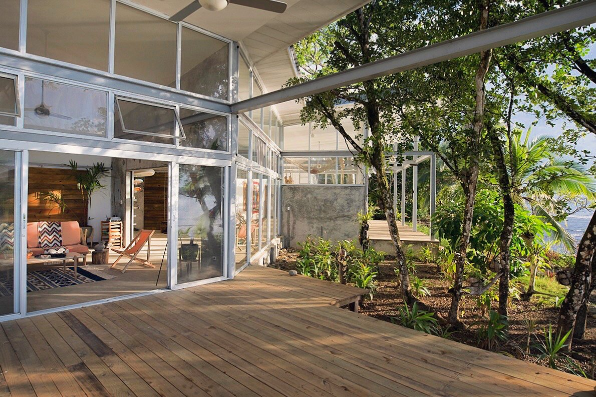 The open plan compound consists of Casa Norte and Casa Sur, two units that share an atrium entryway with large doors that roll open or closed to join or connect the two spaces. Much of the shape of Casa Comunal derives from the existing flora on the site, which includes many fruit-bearing trees.  Photo 2 of 9 in A Community-Oriented Vacation Rental in Panamanian Paradise