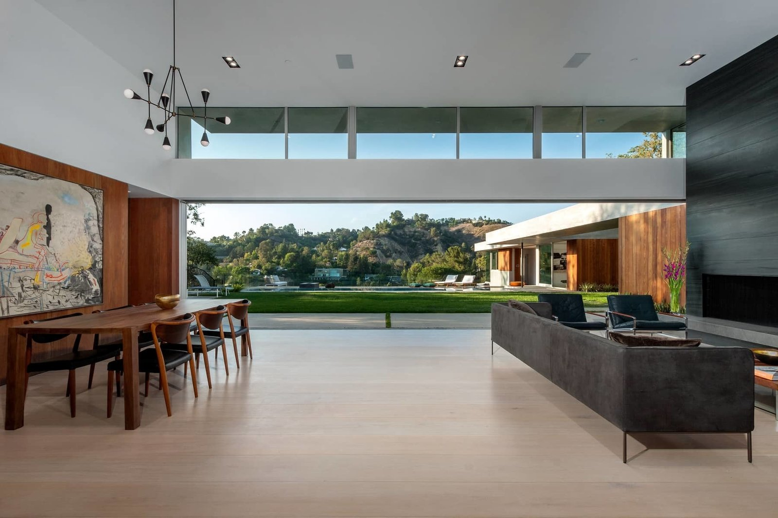 The open plan living and dining areas benefit from a long clerestory window, while sliding doors by Metal Window Corporation blur the boundary between interior and exterior.  Photo 4 of 10 in A Celeb-Worthy Home in Beverly Hills Asks $6.75M