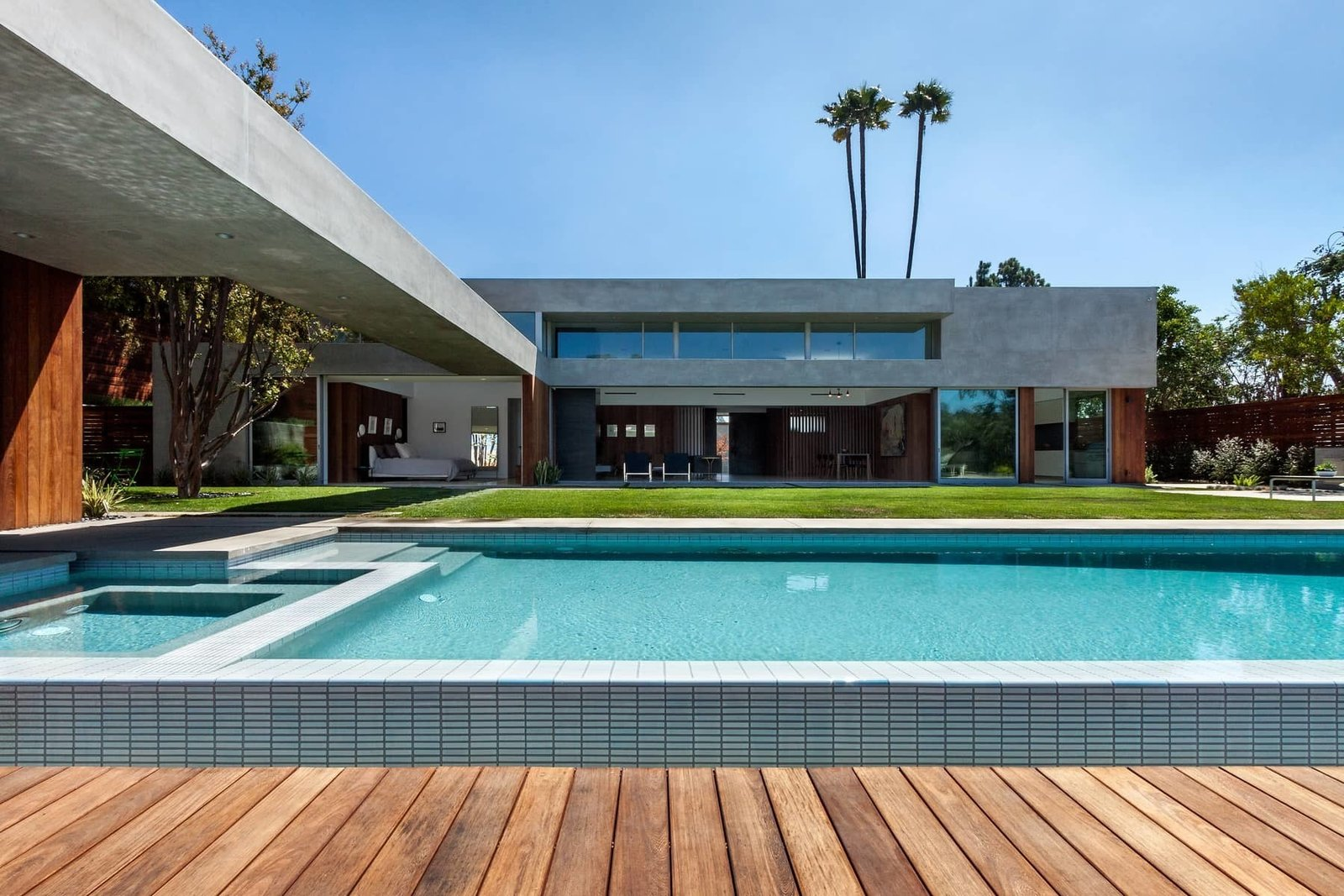 An extended wood terrace surrounds the pool, creating a courtyard setting.  Photo 8 of 10 in A Celeb-Worthy Home in Beverly Hills Asks $6.75M