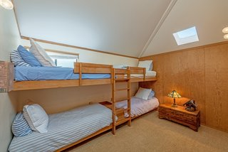 A bunk room in the guest wing sleeps four, ideal for family reunions or bigger groups.