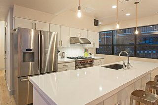 The kitchen boasts white quartz countertops and stainless steel appliances.