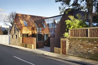 """""""Kew House was conceived as an interplay between the rustic exterior of weathering steel and retained stable wall and the refined, light interior,"""" says Piercy, """"the glazed circulation link revealing the contrast from inside and out."""""""