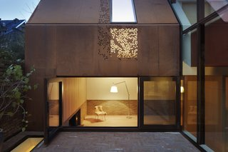 Brick and oak line the interior of the living room, where a wood-burning stove creates a welcoming ambiance. A large picture window opens onto the courtyard. Above, a perforated steel panel allows for an interplay of light and shadow.