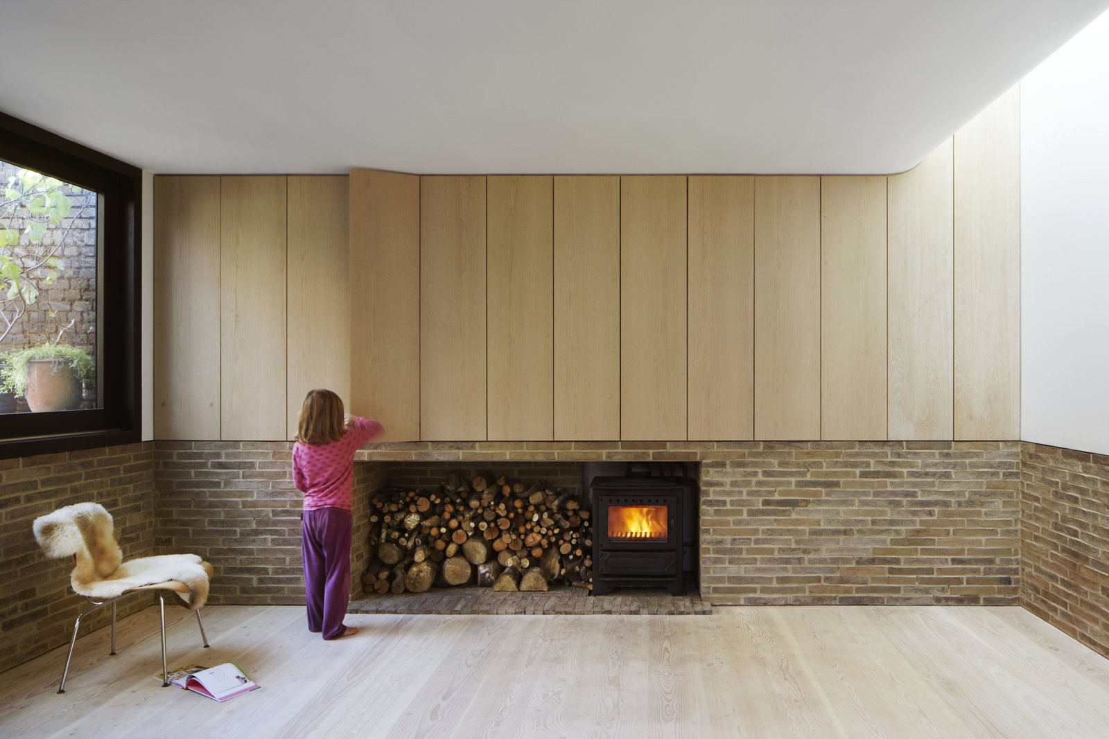 Living Room, Light Hardwood Floor, Standard Layout Fireplace, and Wood Burning Fireplace Bespoke oak cabinetry, produced by an on-site joinery workshop, conceals storage in the living room. A curved ceiling softens the space.  Photo 4 of 11 in Weathered Steel Clads a $4.7M Home Near London's Kew Gardens