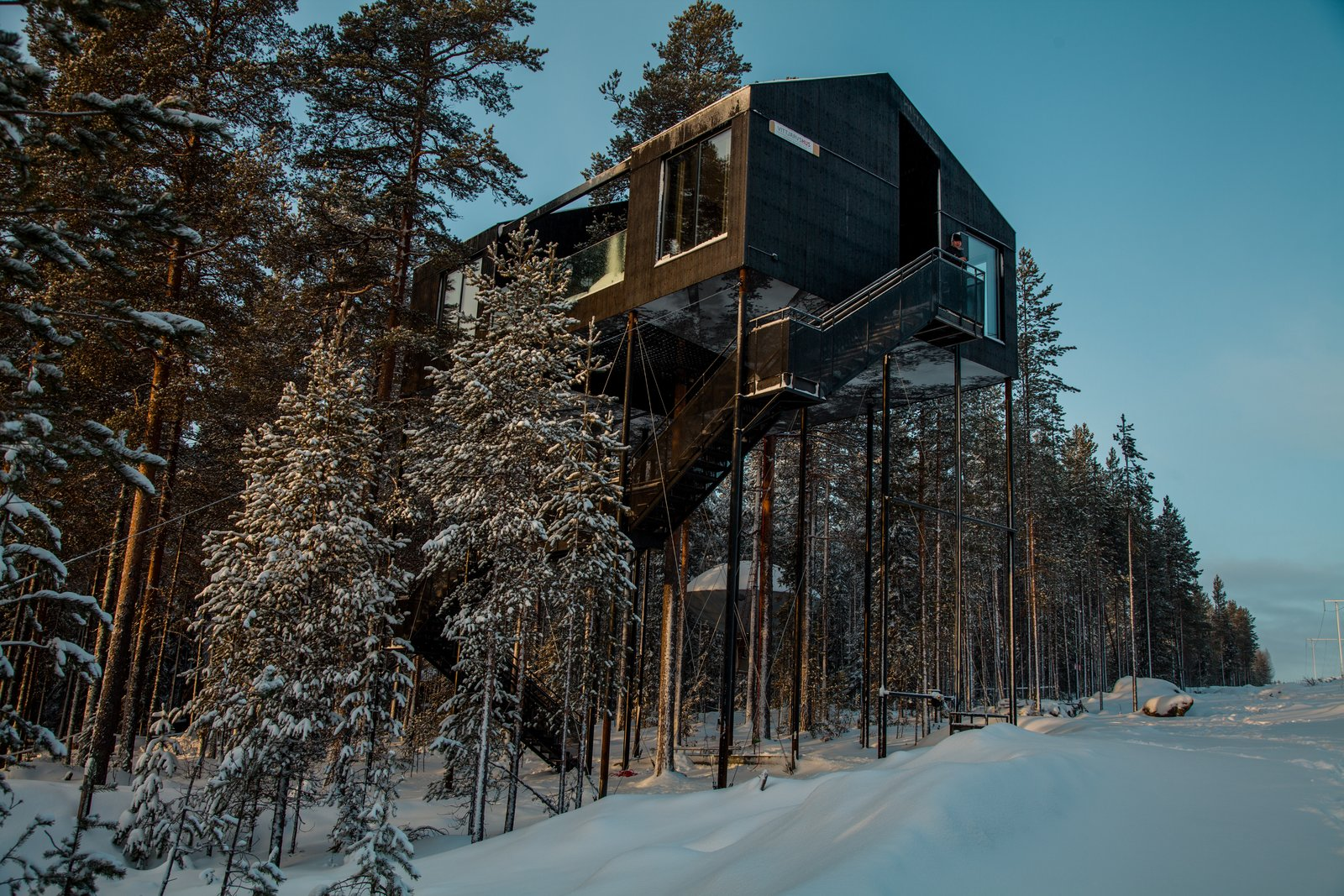 Exterior, Cabin Building Type, and Wood Siding Material As guests approach the cabin from a distance, their view of the structure becomes gradually obscured until the only façade visible is that of the bottom, which bears a print of a pine tree canopy.  Photo 2 of 8 in Go Stargazing in Snøhetta's Towering Addition to Sweden's Treehotel