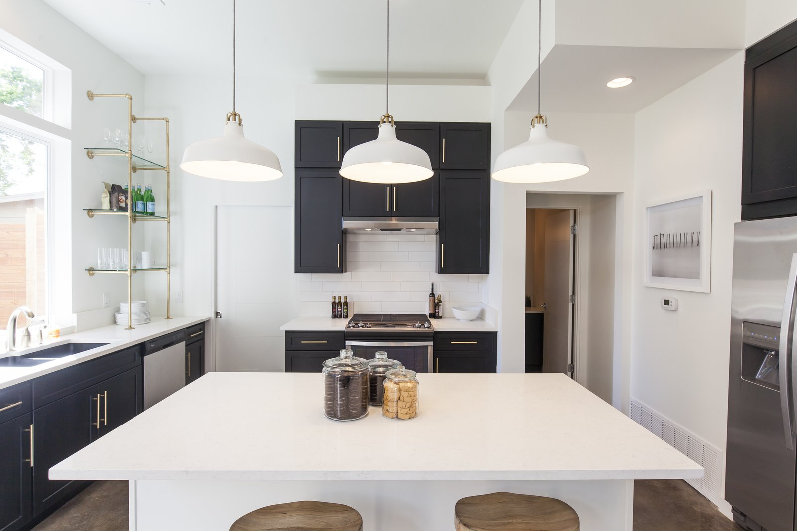 Unit B kitchen with white quartz countertops along counters and island under three white pendant lights.