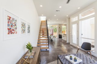 """A stained concrete floor gleams throughout the first floor. """"The staircase is a real showstopper,"""" says Rios, """"connecting to the industrial steel of the containers, but warmed by wooden beams."""""""