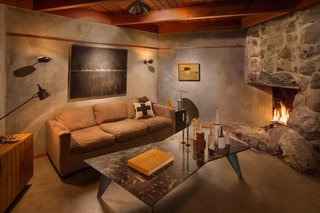 Find Seclusion in the City With This $2.5M Lloyd Wright Residence - Photo 3 of 7 - The den provides a cozy seat by the fire. The original wood beams of the ceilings have aged to a golden brown. To match the hue, Powell has stained the wood used for cabinets, doors, molding, a built-in bed, and wainscoting.