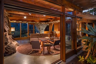 Find Seclusion in the City With This $2.5M Lloyd Wright Residence - Photo 2 of 7 - The integrated living and dining room is contained in an open, hexagonal space with 10-foot ceilings. A long stone wall contains a fireplace, which acts as a divider between the main room and the den. Powell removed the shag carpet that used to run throughout the house and replaced it with concrete topping.