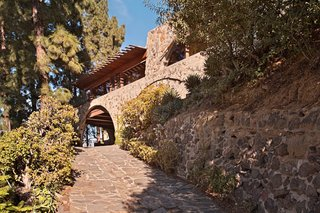 "Find Seclusion in the City With This $2.5M Lloyd Wright Residence - Photo 1 of 7 - A driveway passes under an arch and leads to the rear motor court. The exterior facade of the house is made of stone and concrete, with long bands of windows featuring fir mullions and redwood sills. It also had exterior sheetrock installed in a shiplap style, which Powell replaced with marine-grade fir plywood: ""The white color was jarring and exaggerated any inharmonious detail."""