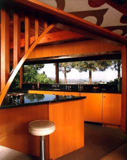 Find Seclusion in the City With This $2.5M Lloyd Wright Residence - Photo 4 of 7 - Powell removed a wall and walk-in pantry to allow the living and dining areas to flow into the kitchen, which is triangular with a granite countertop inlaid with aluminum terrazzo divider strips. He constructed an arched opening with the same radius in the stone arches in the adjacent exterior wall, keeping harmonious proportions throughout the home. The new, straight-grain fir cabinets match the ceilings as well.