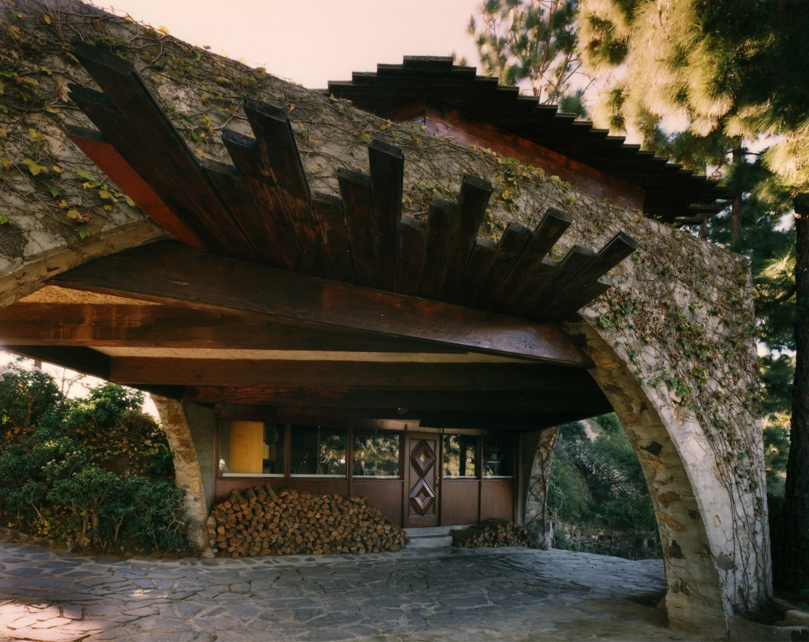 An office space is tucked under the arch spanning the driveway.  Photo 8 of 8 in Find Seclusion in the City With This $2.5M Lloyd Wright Residence