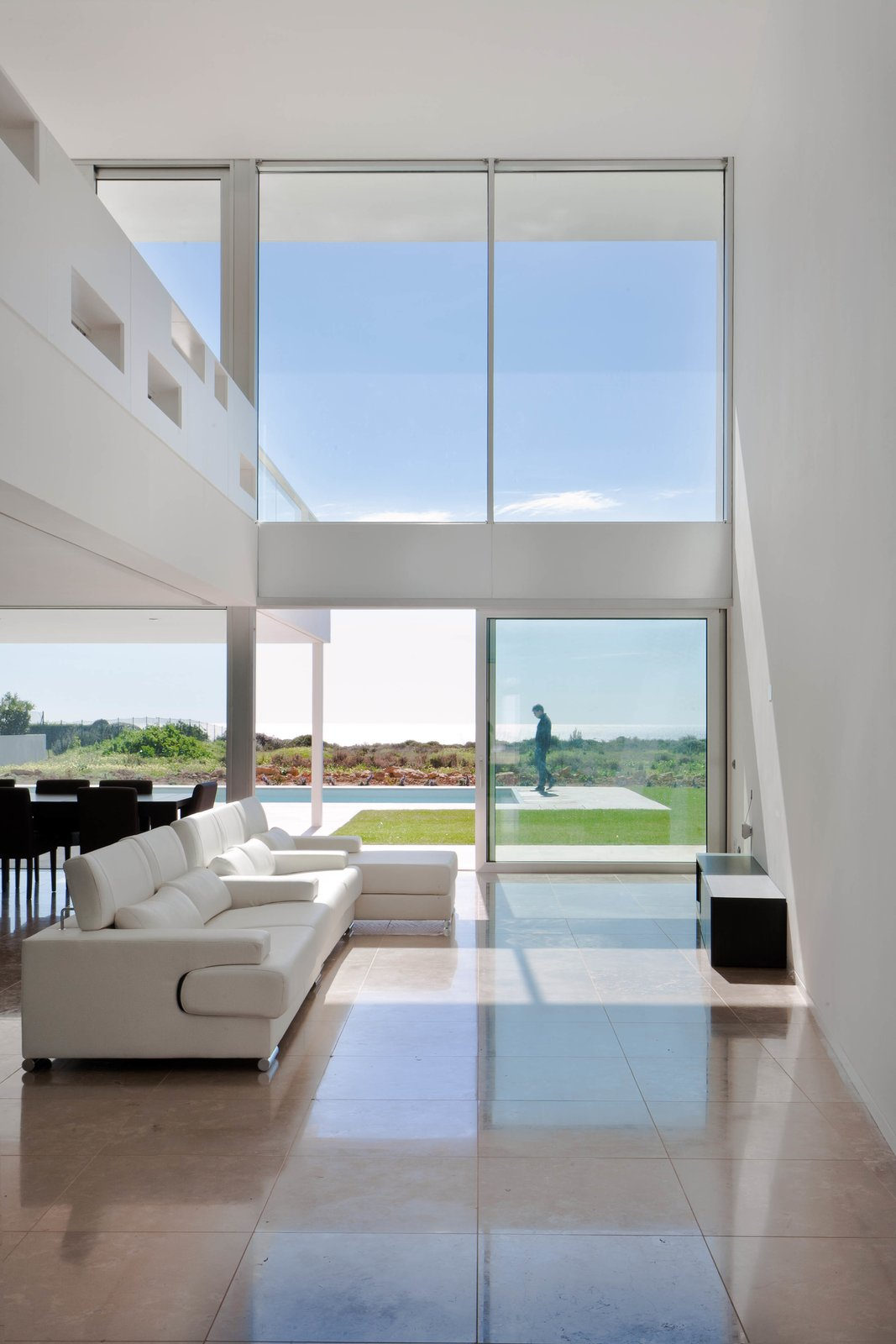 The open kitchen, dining, and living area boasts high ceilings above and natural stone tiles below. Sliding glass doors lead to the outdoor patio and heated pool.  Photo 2 of 8 in Spotlight on Portugal: 7 Epic Modern Spaces from Make This Seaside Villa in Southern Portugal Your Own Private Resort For $2M