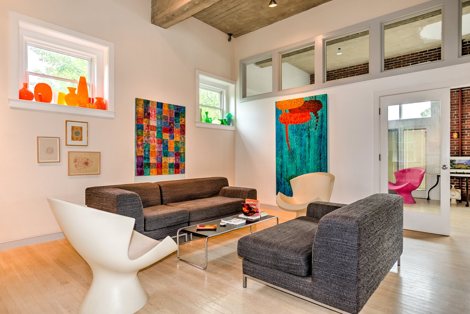 Label Kite Chairs by Karim Rashid flank either side of the living area. Clerestory windows let in additional light.  Photo 4 of 9 in A Converted Firehouse Fit For an Artist Is Listed at $749K