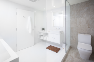 """We kept to a very simple and streamlined palette and carefully selected light fixtures that echoed the lines and movement within the space,"" says Misra. The monochromatic bathroom features a custom white lacquer vanity and Porcelanosa tiles."