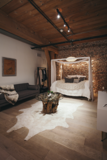 "The sleeping area is tucked into the back of the loft. Says Misra of the clients, ""As they moved in and felt the energy of the place, they admitted they could see themselves staying here more and more and commuting less and less."""
