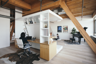 "The Writer's Block is a piece of custom oak veneer millwork that both divides the space and acts as furniture. ""It can be used as a place to lounge, or as a place to retreat and write, or as a place to entertain, and sometimes as a place to just sit and meditate,"" says design principal Chinmaya Misra of the flexible piece."