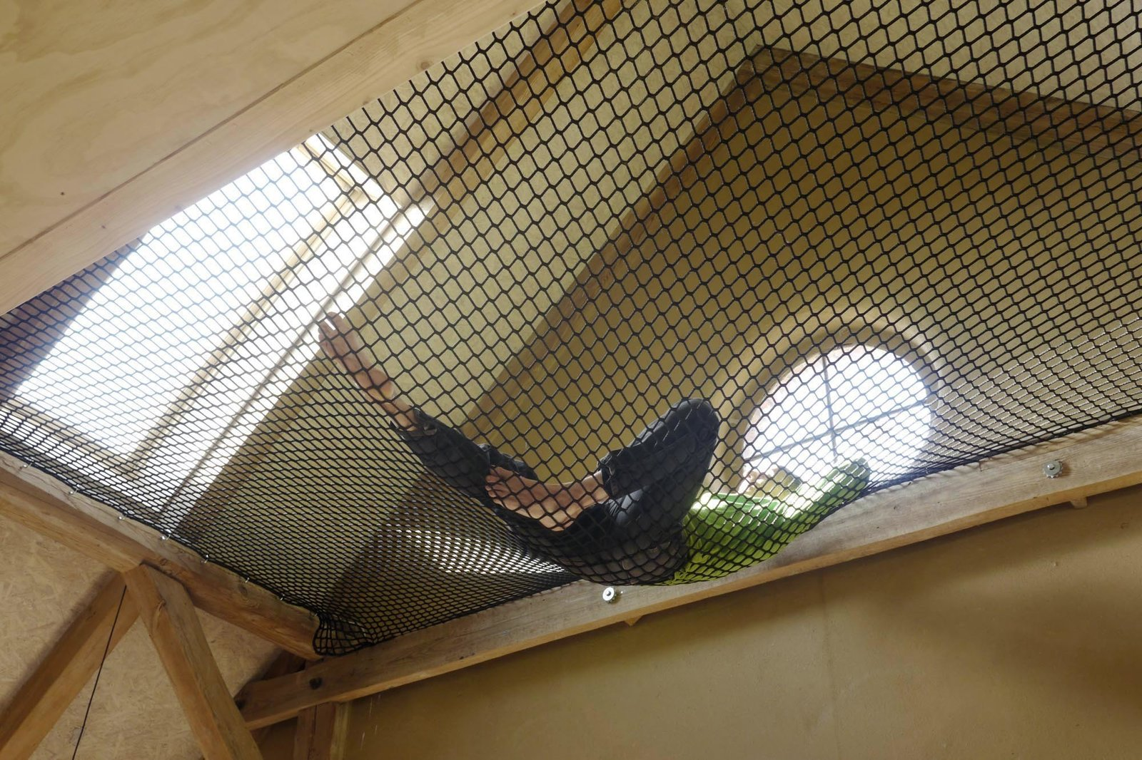 A hammock hung between beams, accessible from the mezzanine, provides a sunny spot to lounge.  Photo 4 of 10 in Rescuing a Historic Homestead, Two Artists Create a Rural German Retreat