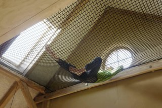 A hammock hung between beams, accessible from the mezzanine, provides a sunny spot to lounge.