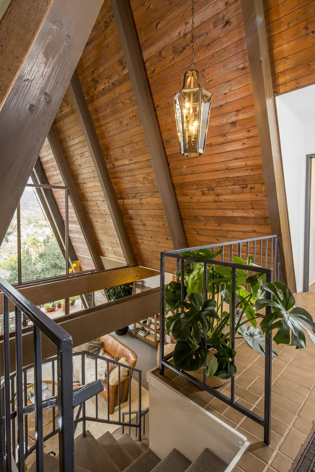 Upon entering, the foyer offers dramatic views of the San Gabriel Mountains straight ahead, framed by the wooden beams of the steeply pitched roof. On either side of the foyer are the master suite and second bedroom.  Photo 3 of 10 in A Modified A-Frame Overlooking Los Angeles Starts at $699K