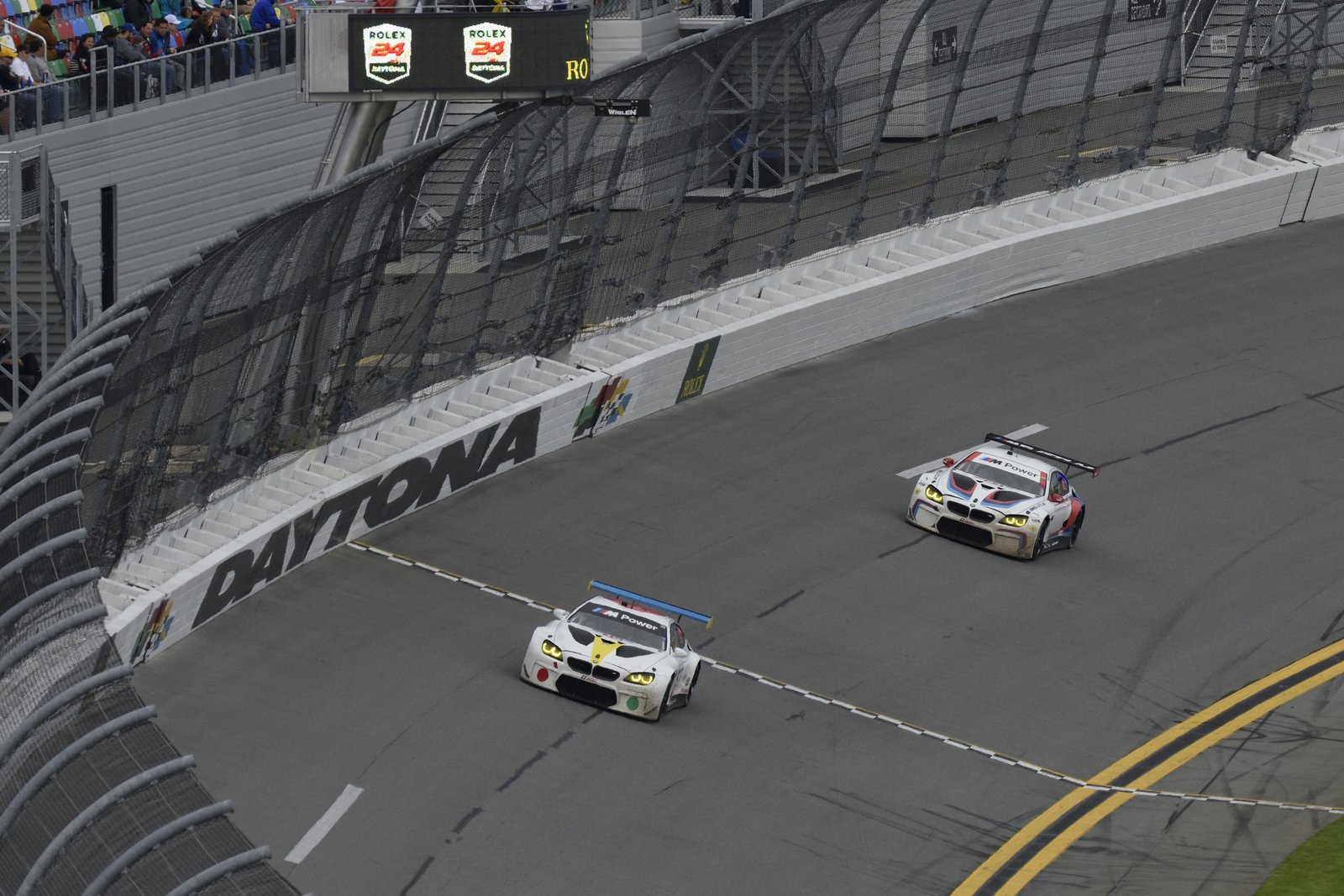 At the start of the race, the BMW M6 GTLM #24 keeps pace with #19. Unfortunately, vibration at the rear of the car takes it out of commission after 14 laps around the Daytona International Speedway.  Photo 8 of 12 in John Baldessari Blazes a Trail at the Daytona International Speedway With BMW Art Car #19