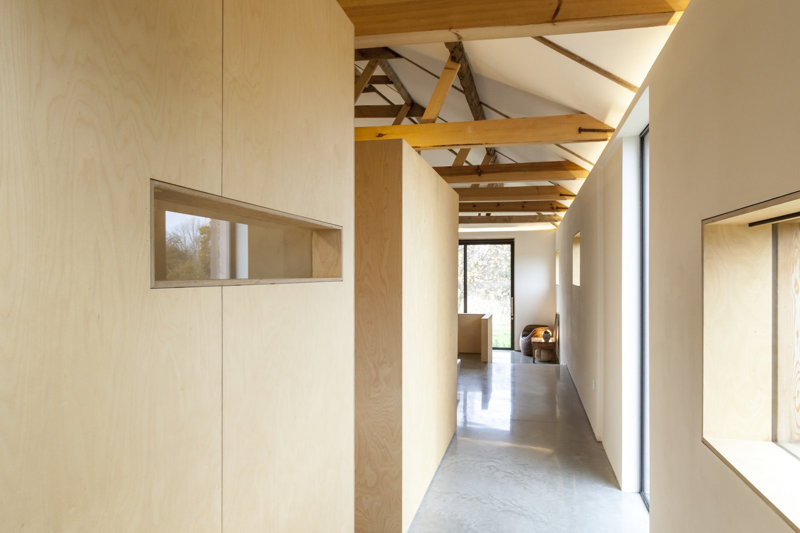 Simple plywood, cut out to allow views of the landscape, creates subdivisions within the home for private bedroom and bathroom spaces. Rather than formal rooms, they have the effect of large-scale furniture. Tagged: Bedroom and Wardrobe.  Photo 9 of 10 in This Converted Barn in the English Countryside Stays True to its Historic Roots