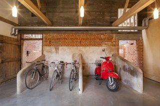 The clients worked with Nossiter to preserve as many historical features as possible. The barn's cruciform plan arose from the model farm movement championed by original owner John Gurdon Esquire, who brought different farming functions under one roof. Here, what was once the old milking parlor now serves as bike and scooter storage.