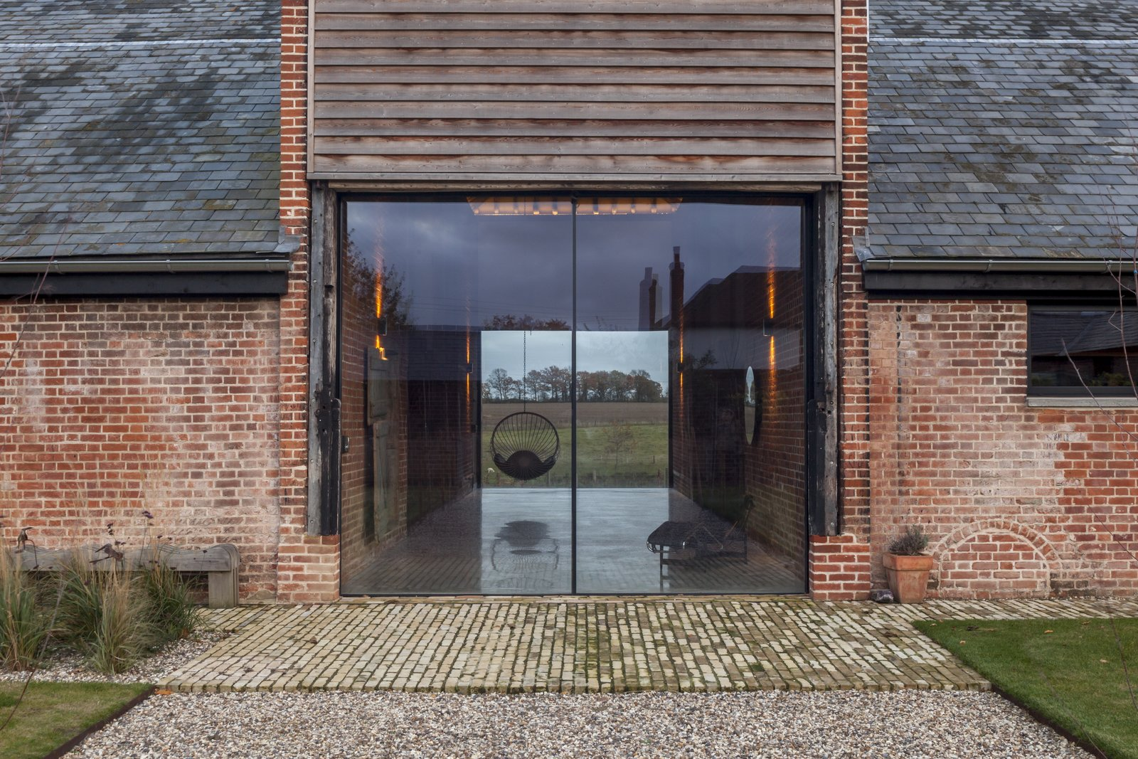 Hallway Two oversized glazed sliding doors welcome guests into Church Hill Barn.  Photo 2 of 10 in This Converted Barn in the English Countryside Stays True to its Historic Roots