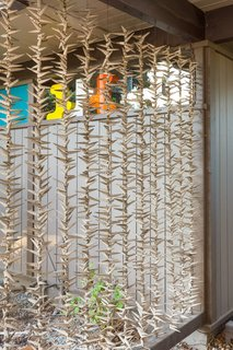 Snag This Midcentury Stunner in Southern California For $799K - Photo 2 of 10 - Strung seashells make up an organic screen for the carport, a natural touch added by the seller.