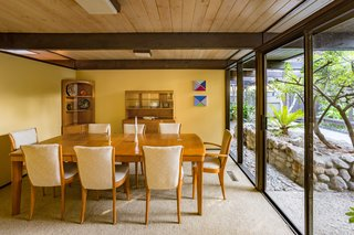 Snag This Midcentury Stunner in Southern California For $799K - Photo 7 of 10 - Homeowners can choose to eat in the dining room, pictured above, or bring their meal to a glass-encased lanai that looks out at the grassy backyard.