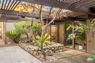 Snag This Midcentury Stunner in Southern California For $799K - Photo 8 of 10 - The dining room and bedrooms lead to a large garden patio.