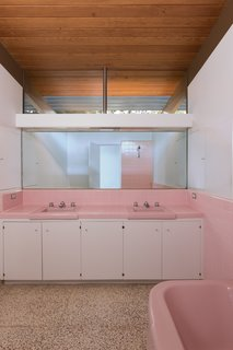 """The three original bathrooms were each designed in a different pastel color: pink, yellow, and blue,"" says Cole. These were mostly intact, though the homeowners reinstalled the colored Crane toilet in the master bath, pictured above. The restorers polished the original terrazzo flooring."