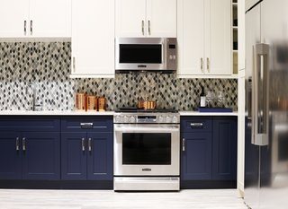 "The Signature Kitchen Suite Smart Kitchen is outfitted with navy and ivory cabinets by Green Forest Cabinetry and a glass tile mosaic backsplash. For Fuller, who comes from a product design background, the ""smart thinking"" of the brand's designs put them ahead of the curve. For example, the Gas Slide-In Oven Range above has an Easy Swivel Handle that is easier and safer to operate, and the capacious refrigerator benefits from a SmartSpace System ice dispenser that maximizes storage space."