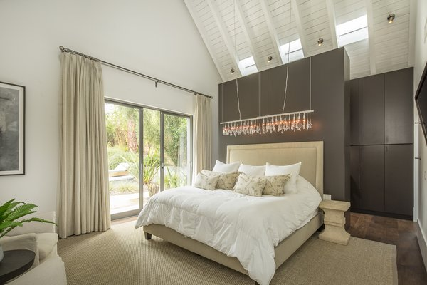 """Like all the bedrooms and bathrooms, the master bedroom has electric venting skylights, as well as a sliding door that leads to the back patio. """"Sleeping at night, you can throw the doors and the skylights open, and you get beautiful, natural circulation into the house,"""" says Van Scoter. Behind the bed is a dark wood wardrobe that feeds into the en suite bathroom."""